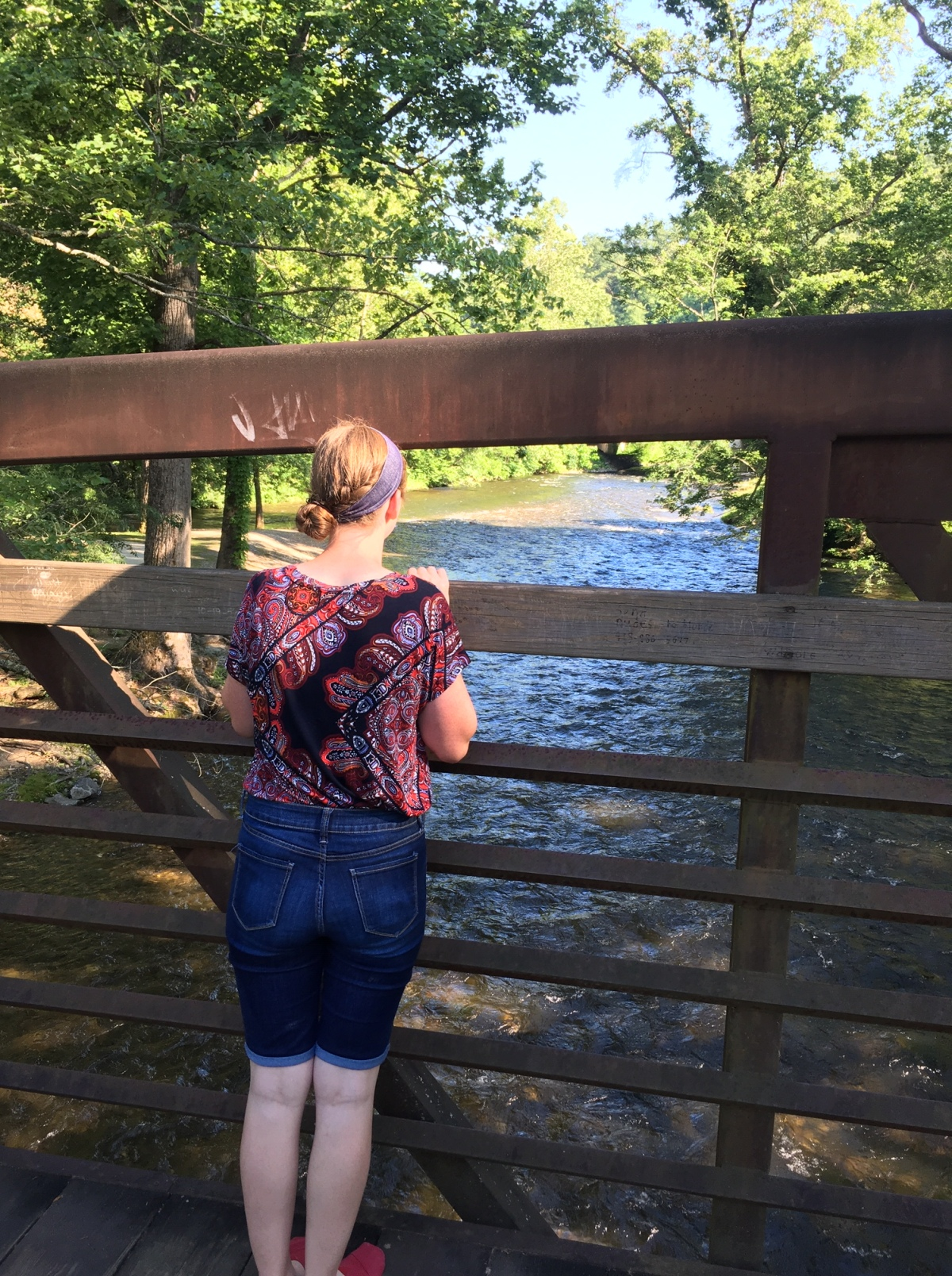 Girl on a bridge looking at the river